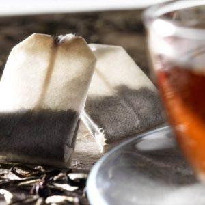 particolare tazza di the su piano di legno con bustine di theesclusiva tipsrealese: tutti gli utilizzi